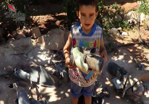 صورة طفل من قرية  -عين لاروز- يحمل ما تبقى من إحدى صواريخ الراجمة التي سقطت بجوار منزله .
